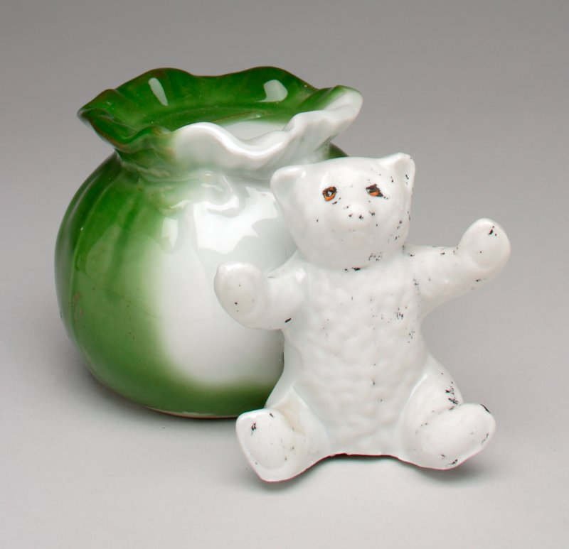white bear seated in front of green and white sack; coin slot in mouthsof sack