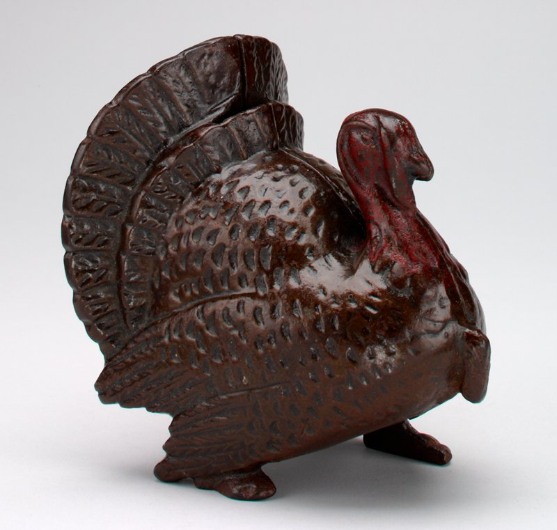 metal standing turkey with spread tail; coin slot at top of tail; red head and face; made in 2 halves held together by a screw