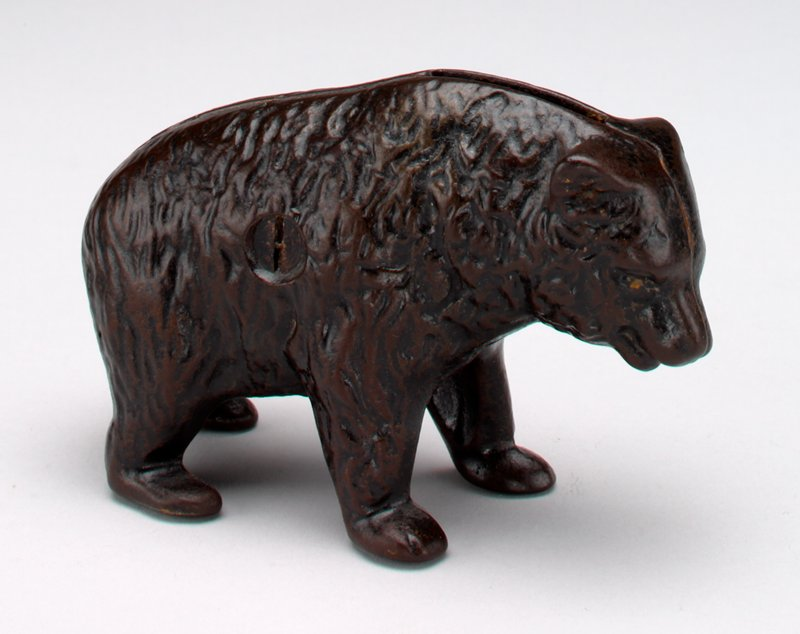 small standing brown bear; red tongue; coin slot in back of neck