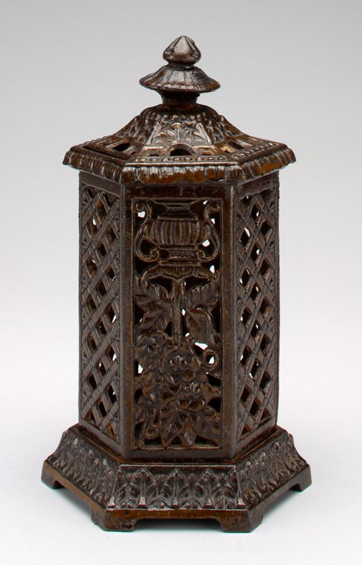 metal six-sided pagoda shape with lattice on 4 sides and open work vase and flowers on 2 sides; floral motifs around the base and top; coin slots on 2 sides of top