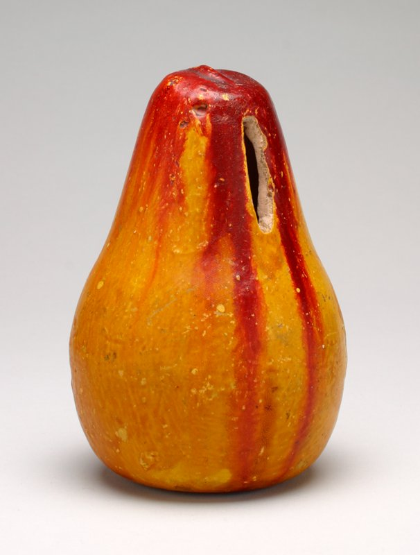 ceramic pear, yellow and red; coin slot in top third of body; glazed