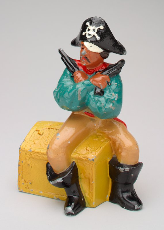 pirate with crossed arms and 2 pistols sitting on a gold treasure chest; he has black boots and black hat with a skull and crossbones