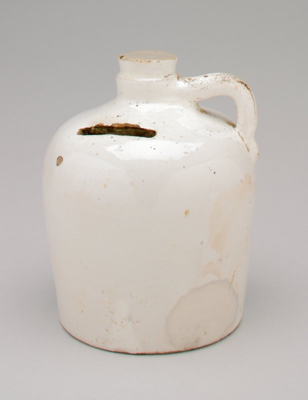 white glazed ceramic jug-shaped bank with coin slot in shoulder of jug; has handle and stopper with gray top