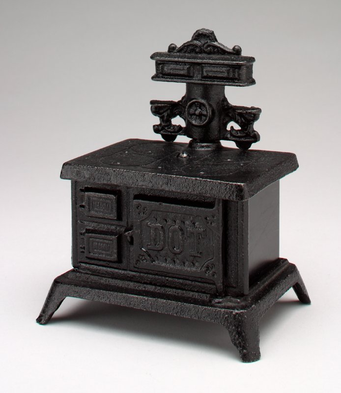 """old-fashioned black cook stove on 4 short legs; 4 burners on top with separate pipe on top; 3 doors on front, one door opens and says """"Cook with Cash""""; on the outside of thelarge door is printed """"DOT"""""""