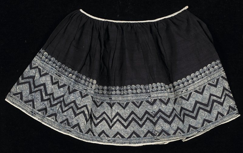 """blue skirt with light waistband; lighter bottom trim (approximately 9"""") has a double row of circles, then double row of horizontal stripes with X's in between; wide row of zigzags and final pattern repeats horizontal stripes with X's"""