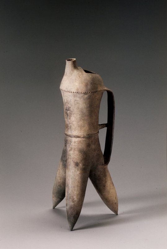 very thin walls; tube-shaped body with three thick, tapering, splayed feet; rounded top with short spout and half-circle-shaped opening; handle decorated with incised lines and v's and applied circles