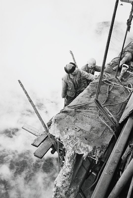 two men on wood plank platform holding onto crumbling cement (?) beam; leg and part of torso of third individual visible on beam; background smoke or haze