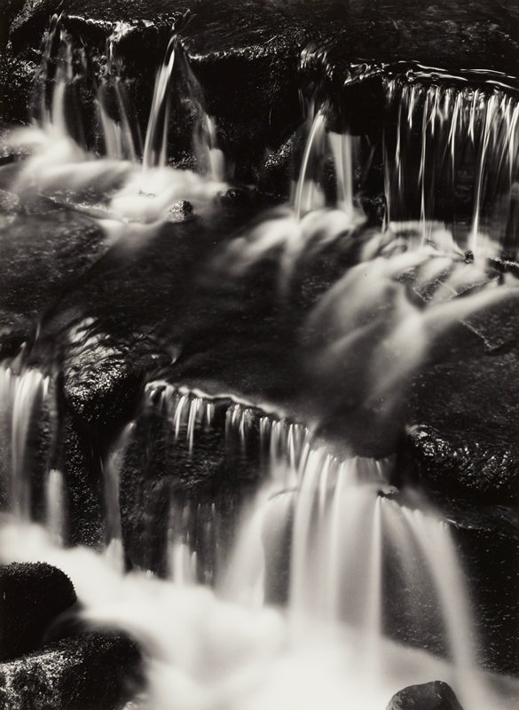 two cascades of water falling down rocks; mist at each level