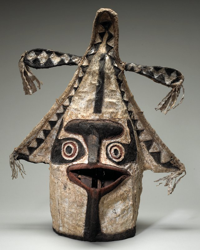 mask with beak-like mouth, heavy brown brow and nose and round eyes of red, white and black; point at top of head with fringed crosspiece; black star on back of head