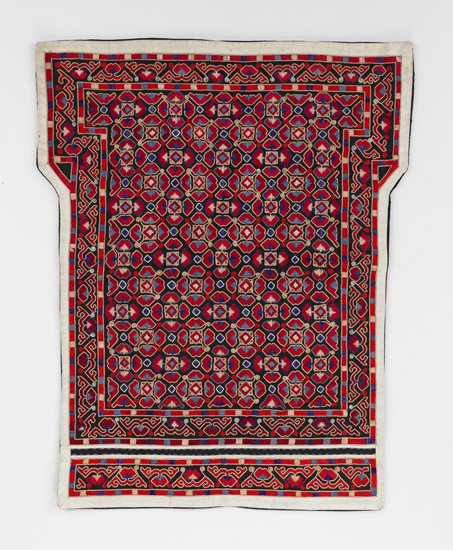 """two inch border pattern surrounds central slight """"T"""" shape; 2 1/4"""" overlapping abstract floral pattern outlined in chain stitch; red, blue and tan colors; 3/4"""" white border outside edge; dark blue indigo lining"""