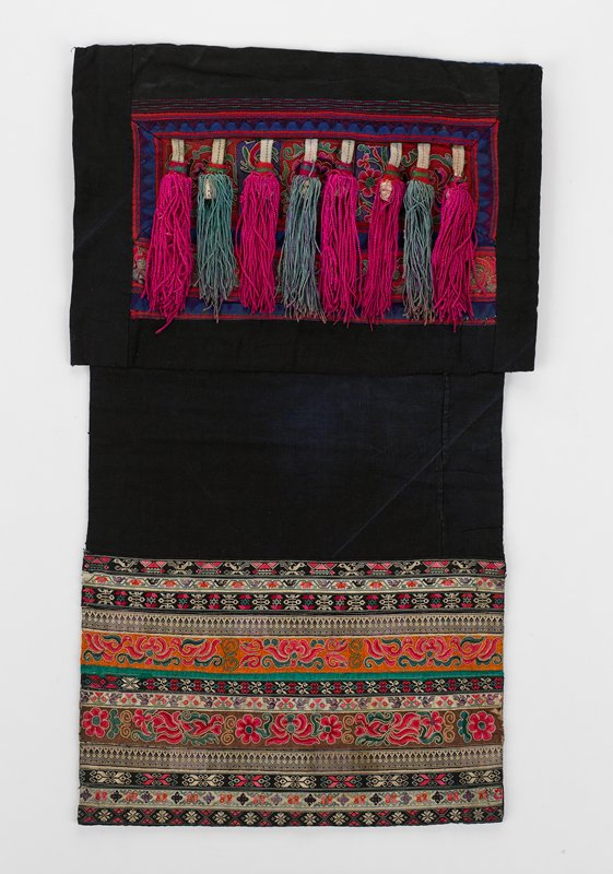 """top black section has two red embroidered appliques, one damask, floral patterns, bordered in blue; eight 7"""" tassels in pink or teal hang loose from blue border; lower indigo section has 10"""" of 13 hand and commercial embroidered stiprs; multicolored; blue lining"""