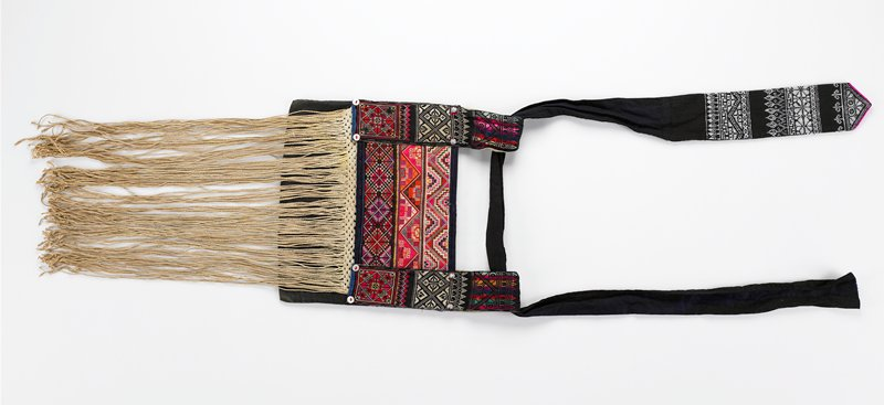 "bag: black with red and multicolored embroidery; 3 wide bands of embroidery on front with 3 smaller bands on each side, froming loops; four shell buttons and four raised metal discs finish design; black bag lined with coarse, heavy tan fabric; 15""-16"" woven and knotted fringe down front; geometric embroidered patterns; sash/strap: black and white; black sash with 11"" of white embroidery on one end; floral and geometric designs; pointed end edged in bright pink (looks very Nordic)"
