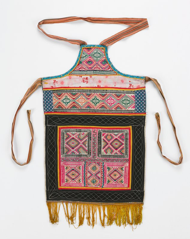 """pink, black and white; gold fringe; printed fabric and embroidered strips and squares; satin stitch outlined with machine stitch designs; lined in blue plain and printed fabric; ties 26 1/2"""" long; neckband 36 1/2"""""""