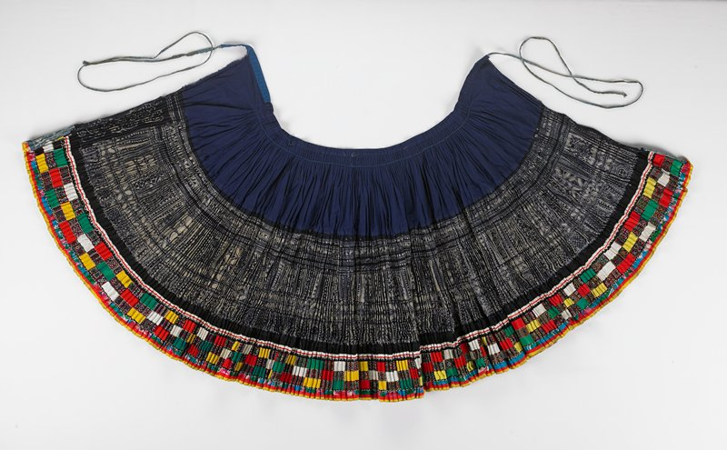 pleated skirt with 3 sections; blue top and band with pleats hand stitched down; batik middle; two layer bottom section with outside multicolored cross stitched rectangles; inside bottom is batik; 2 narrow ties
