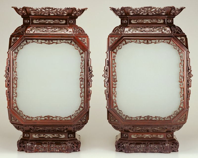 four-sided carved wood lantern with glass panels; metal hardware at top for hanging