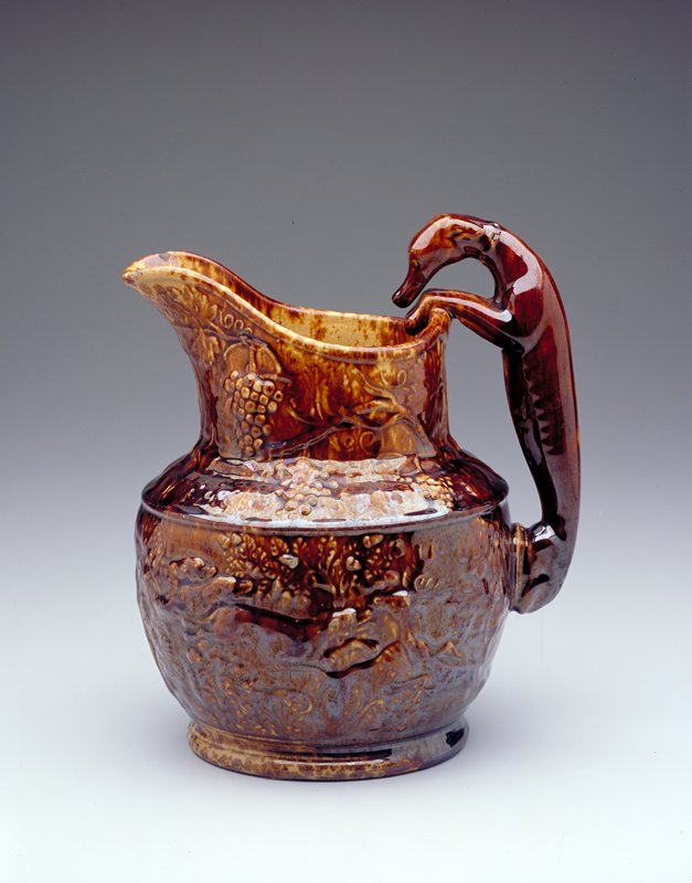 pitcher, large, whippet handle, animal and fruit pattern around body of pitcher, yellow-brown glaze