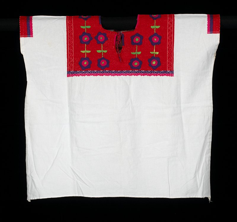 one white panel cotton fabric huipil; red hand embroidered on top with flower decoration; armholes are also decorated in red, purple and pink stripes; neckline has a fine hand-sewn seam