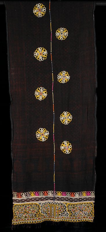black and dark red resist printed fabric; decorated with nine yellow and white embroidered medallions with raised mirror centers; multi-colored embroidered strip down center; each end heavily embroidered with small mirror patterns (multicolored); two selvedges; two fringed ends