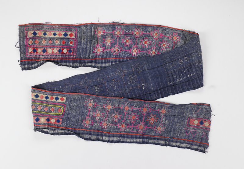 faded blue batik fabric divided into three sections of 14 red outlined eight-pointed stars and red square center appliques; three other sections are horizontal strips with square applique centers of fabric, some with patterns, some red, white and blue, bordered by red and yellow yarn