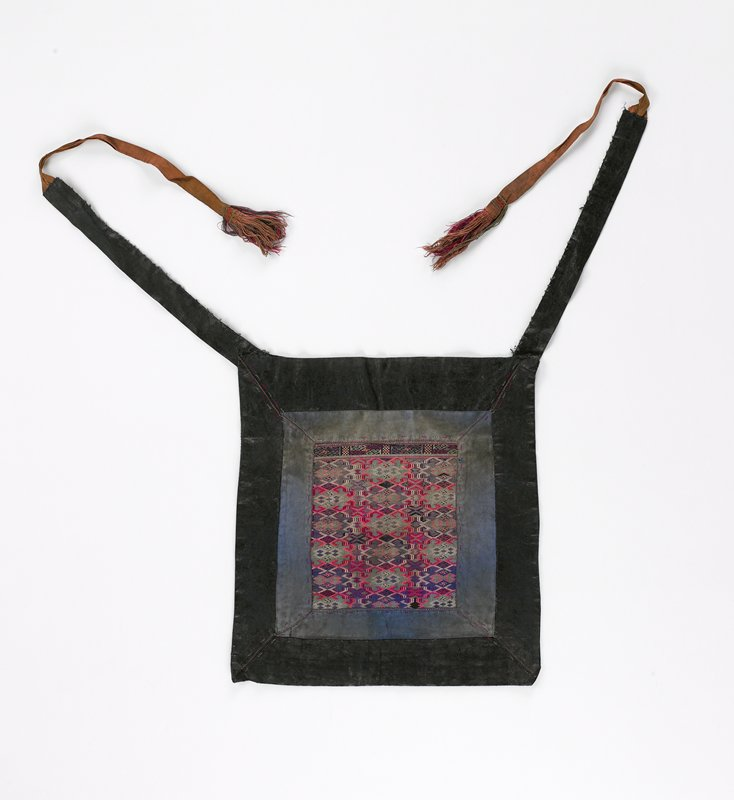 center embroidered section is geometric, mainly diamonds, in blue; cotton frame set in pounded indigo frame; ties on upper corners with tassels; red, purple, green on black