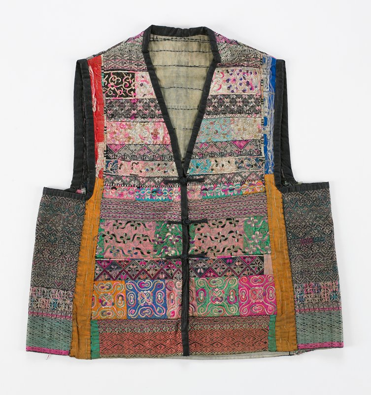 lined; horizontal pieces of varying widths, designs, materials and colors; some geometric, some floral; armholes, front and neck bound in dark indigo; three frog closures with knotted buttons; inserted colored vertical strips in various colors
