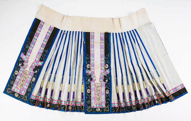 two-panel silk wrap skirt; plain tan cotton waistband; left sections of each panel heavily embroidered, centering on a depiction of a figure in garden scene framed by ribbon and applique; right sections have bright blue ribbons fanning down tan brocade and ending in loosely attached points with tassels; black and blue lower border; lined in blue silk
