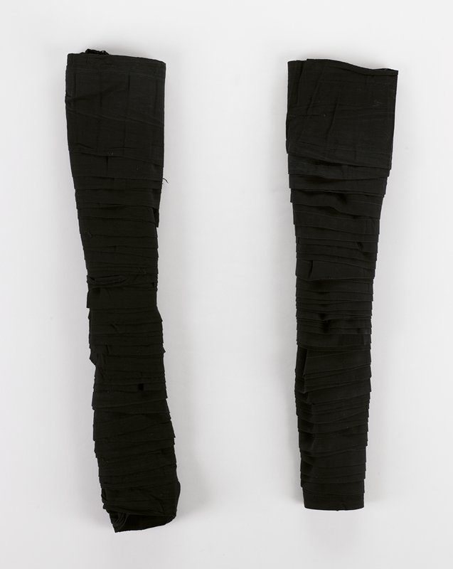 pair of very long narrow plain black wraps with fringe on both ends; selvedge on top, hemmed bottom; selvedged side has numerous machine repaired tears