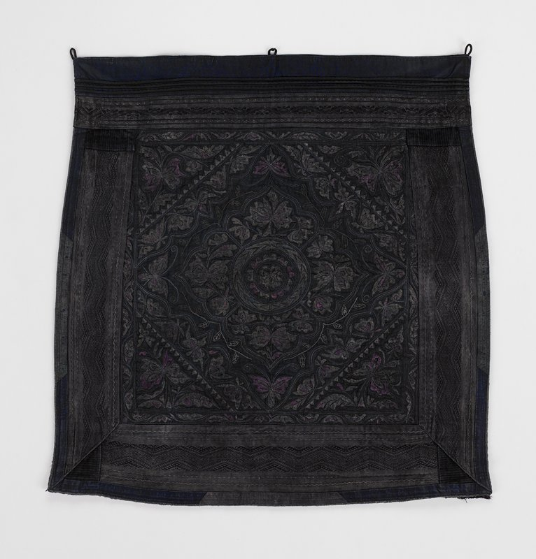 black indigo lining; dark embroidered piece; geometric floral and butterfly designs in shades of pink and gray; surrounded by woven geometric broder--black and grey; narrow pieces edging on three sides; top border has horizontal woven band in black and grey; three attached loops--center and each corner on top