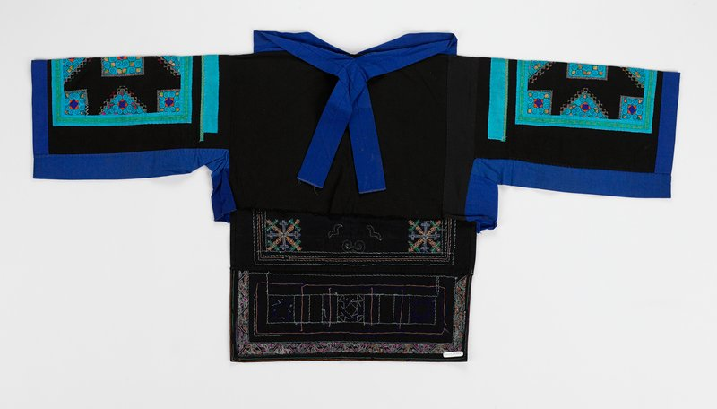 pullover; front and back not determined; black; one side has large teal slik appliqued square frame with cross stitch in red, green and white and appliqued scrolled triangles in teal; tail has appliqued teal rectangle filled with geometric patterns in orange, green and purple; sleeve repeats applique motif; wide stand-up collar with ties and border on sleeves are purple; shorter side is plain black