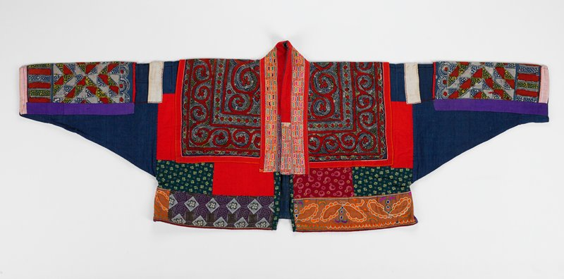 woman's festive jacket consisting of patchwork of batik, embroidery and commerical prints interspersed with solid colors of red, purple, white and blue with blue lining; predominance of red; front opening