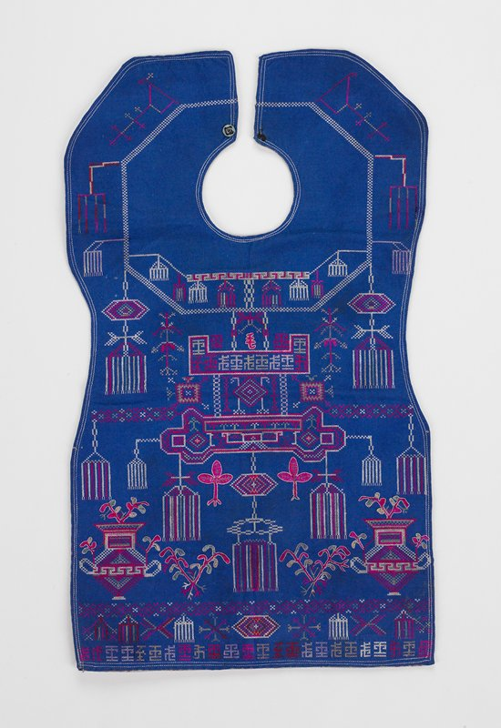 neck fastened with a snap; overall tiny cross stitch patterns set symmetrically; mostly unidentifyable patterns; some floral motifs; medium blue with red, white and green embroidery; lined with commercial floral fabric