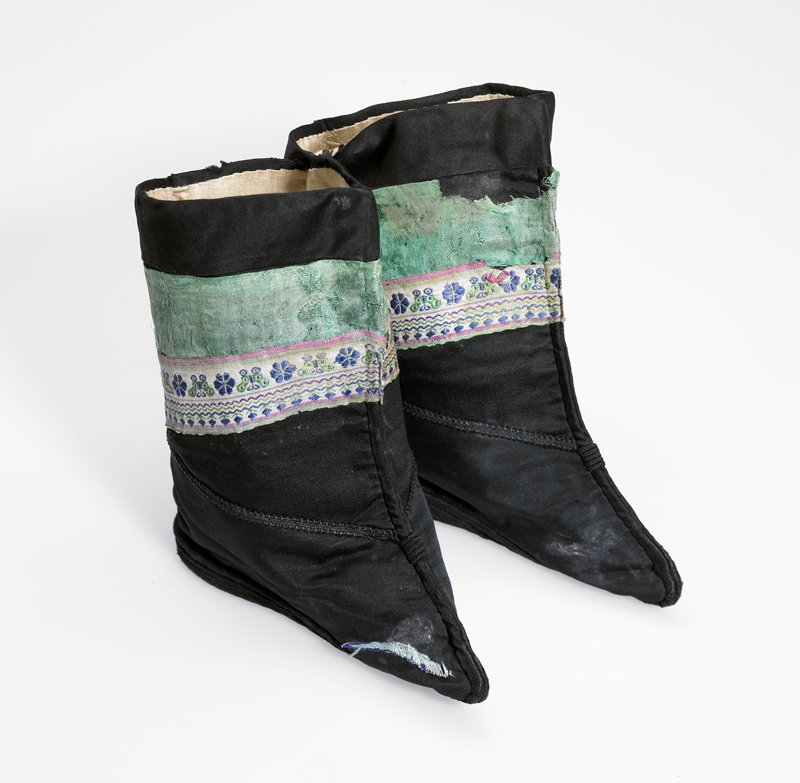 "boot with white lining; black silk boot with applied (glued?) green embroidered 2 1/4""band; black braid applied on ankle; pear shaped elongated stiff stitched sole doesn't cover very pointed toe area; PR toe has applied green decoration; other toe areas show evidence of missing decoration; boot a: paper label on inside PR with mark E25; tied together"
