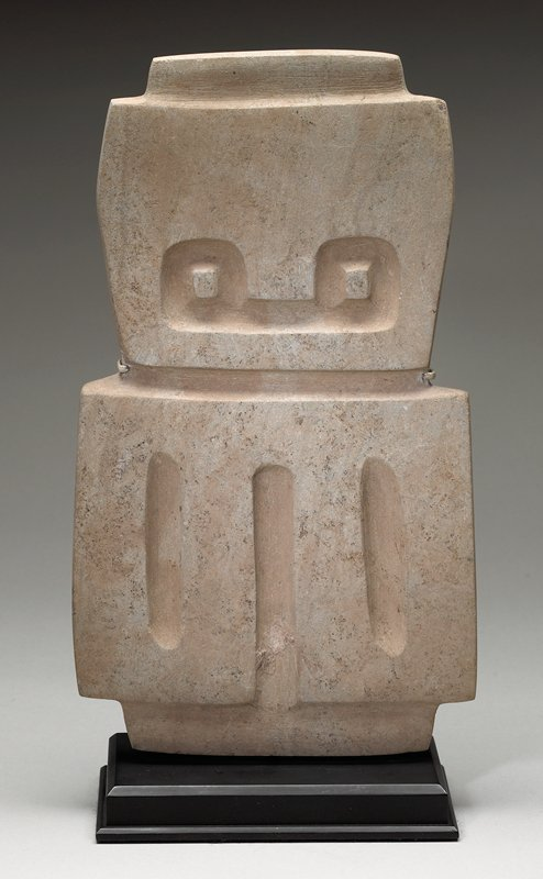 flat stele with square body and square head; three vertical indentations on body; owl-looking eyes on head; grey/ beige in color