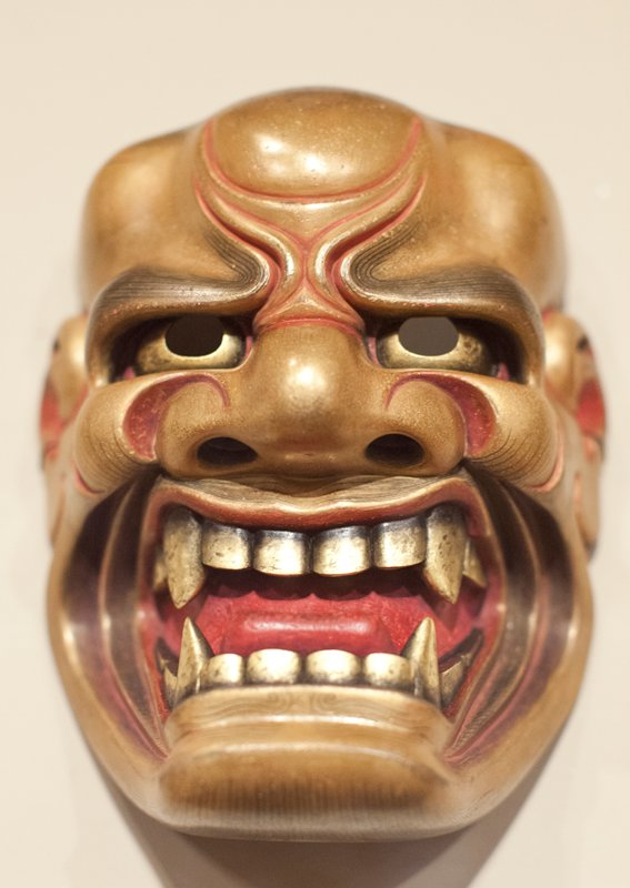 growling lion/demon face with gold and red skin, very wide nose and gold teeth; large red tongue; upper palate, irises, nostrils and ear canals cut out