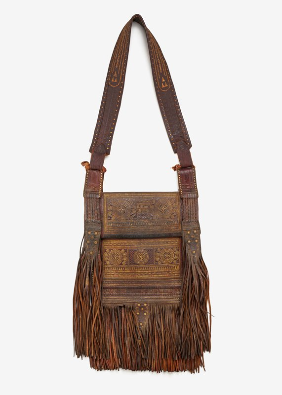 bag with shoulder strap; stamps on leather on strap and front and back of bag with decorative stitching on strap and front of bag; long fringe with tassels on bottom of front flap and sides