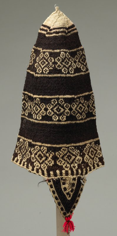 peaked black knit with bands of white designs; applied flaps have red wool tassels; twisted yarn forms ties