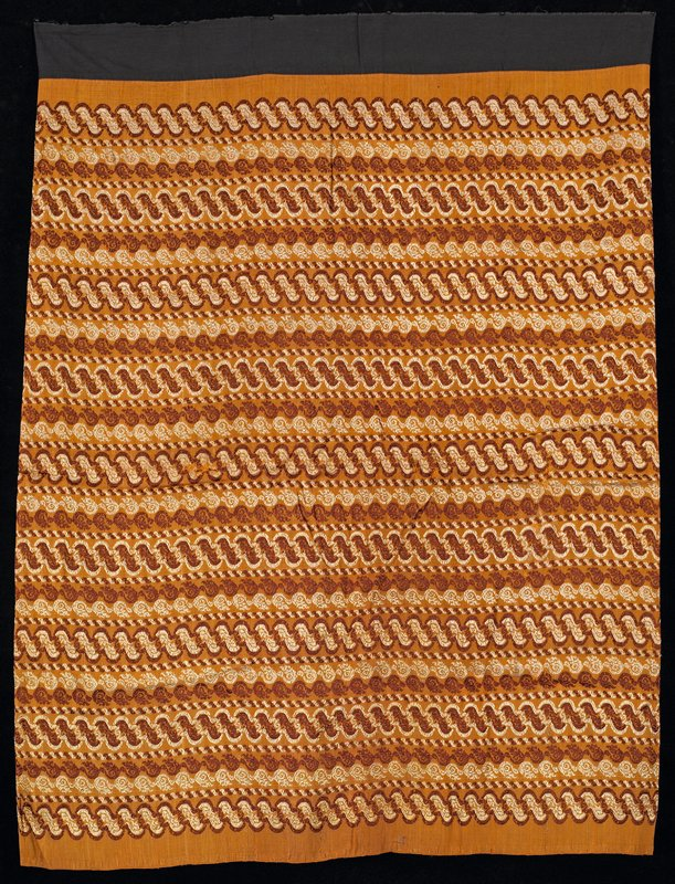 horizontal rows of soft wavy designs in rust, beige, on orange field; black waistband