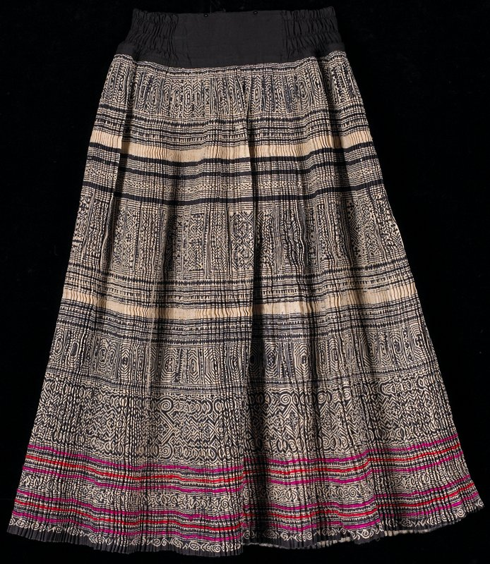 resist dyed blue/black and white; tightly pleated with six rows of narrow red and pink trim along bottom; zipper fastener in back; black elasticized waistband