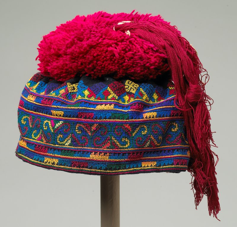 "lined hat with overall cross stitch embroidery with large red pompom and two tassels; red, green, blue, yellow and brown; 4"" loop of thread attached to back"