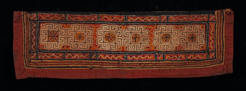 dark red; pirmary design has six embroidered geometric shapes; bordered with small strips of applique; black, tan on orange; brown lining