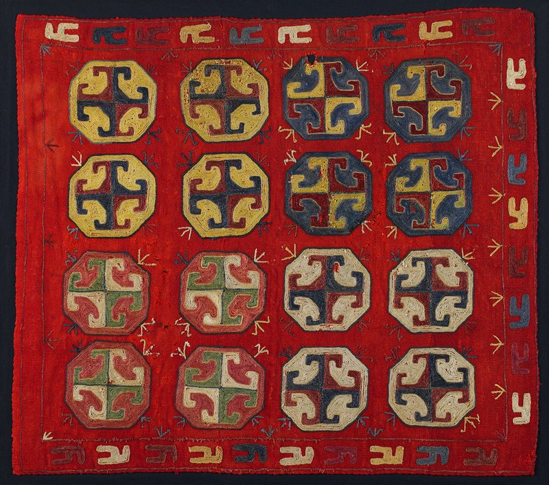 Hand woven red wool horizontally pieced ground with polychrome silk embroidery. The panel is hand stitched at the edges and in a grid pattern, to black cotton fabric. There is no edge binding or backing. The verso is not visible.