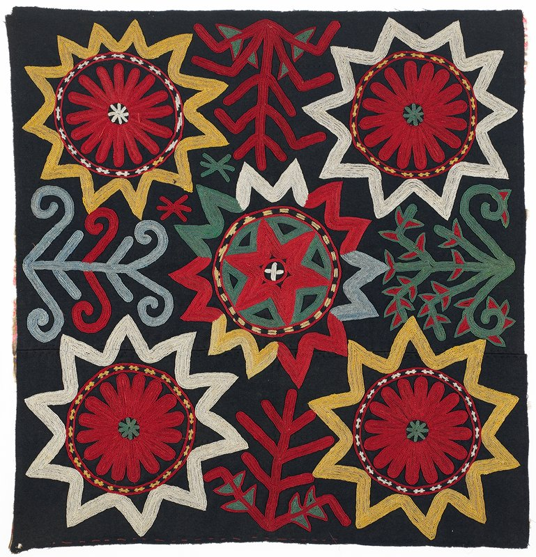 """Black wool pieced ground with polychrome silk embroidery through a printed cotton substrate. There is no binding, edge finishing, or backing. Red basting stitch along one edge for 12""""."""