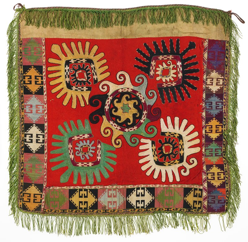 Fringe with plain-weave heading, cloth band, One Jacquard woven band, three wide embroidered bands, Pieced, printed lining. Red wool ground with polychrome silk and synthetic embroidery. The attached bands on the sides and bottom edge are entirely cross-stitched in wilk on cotton. The top band, under the fringe is tan cotton damask. The fringe is cotton, and there is a striped woven cotton binding on the edges. The cotton backing is secured with adhesive.