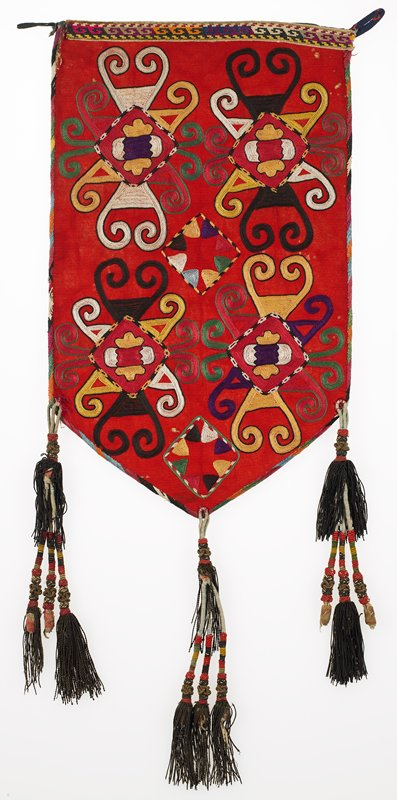 Embroidered band at top, Striped lining. Red plain weave wool ground with polychrome silk embroidery. The diagonally pattered silk edge binding is embroidered. Cotton tape cross-stitched in silk thread forms a border at the upper edge. The hanging loops are cotton. Sewn on tassels are constructed of cotton and metallic threads, in bundles of three. Striped cotton fabric is secured to the reverse of the panel with starch paste, There is no finished backing.