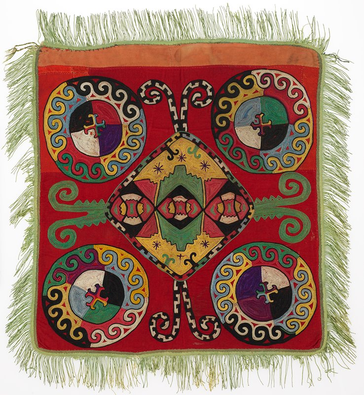 Fringe with warp-twined heading, cloth band . The red ground is pieced from red cotton flannel and red plain weave wool fabrics. There is a pink cotton sateen strip at the top edge under the fringe. The embroidery is worked in silk. Green cotton bias-cut cotton binds the edges. The fringe is green cotton. There is a printed cotton substrate, through which the embroidery is worked. No backing is present. Chain stitch.