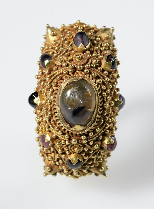 large ring with central cloudy brown-grey gem with dark brown fleck; gold wire filigree work overall with eight other small gems around central stone; small gems in shades of purple and pink