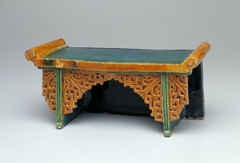 Tomb furniture; table with scrolled short edges on tabletop; apron extending nearly to bottom of legs and short at center with incised geometric designs; flat undecorated slabs at sides and back; scrolls, edges of tabletop and apron glazed tan, other areas glazed green