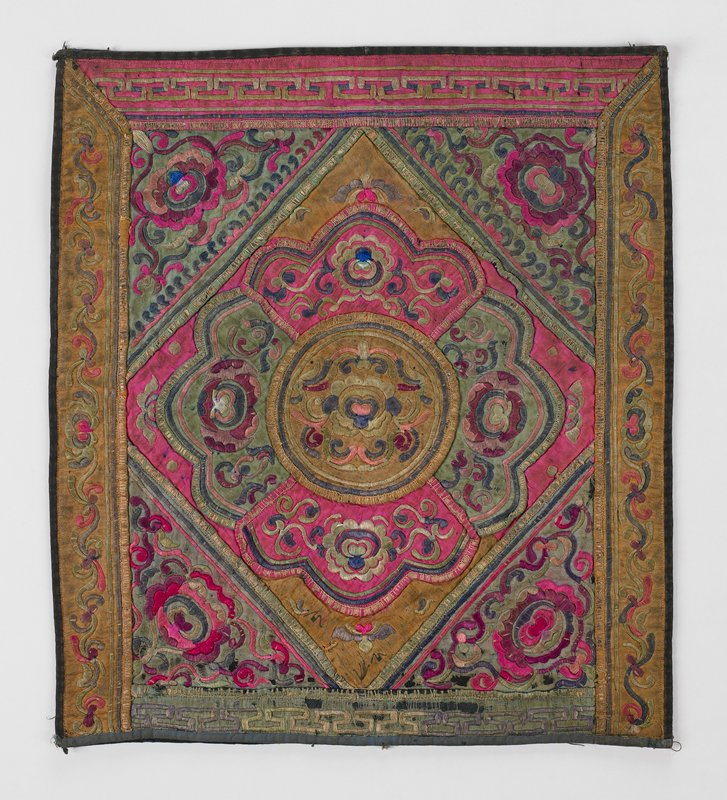 silk center triangle and flower made up of floral embroidered pink, green and gold appliques; corner triangles are green silk floral embroidery; border top and bottom are pink and green silk with running Chinese geometric pattern; dark blue lining, cotton