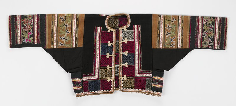 short black jacket with large gussets; heavy geometric embroidery in red, green, white, beige on center fronts, center back and lower edges bordered by purchased tape; five frog closures with metal bell buttons; lower edge has double row of seed trim; metallic gold color narrow tape throughout emboridery; sleeves have beige and black background with large stylized embroidery, tape and metallic tape, in green, blue, black, red and white