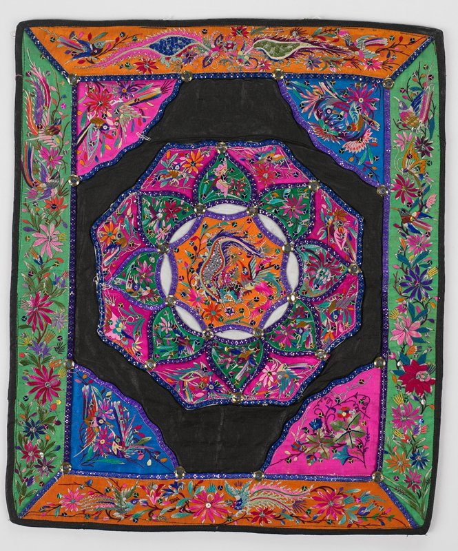 black cotton or linen center has an intricate hexagonal flower formed from two rows of petal appliques in pink and green with flora and fauna embroidery linked around center orange embroiderey with dragon by blue and silver tape leaving see-through white petal shapes; pink and blue triangle corners and orange and green borders repeat flora and fauna embroidery; sequins and mirror-like metal studs throughout; red commercial print lining